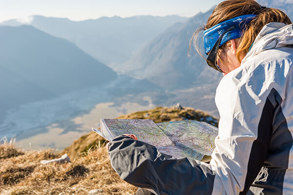 Woman looking at a printed map in nature.